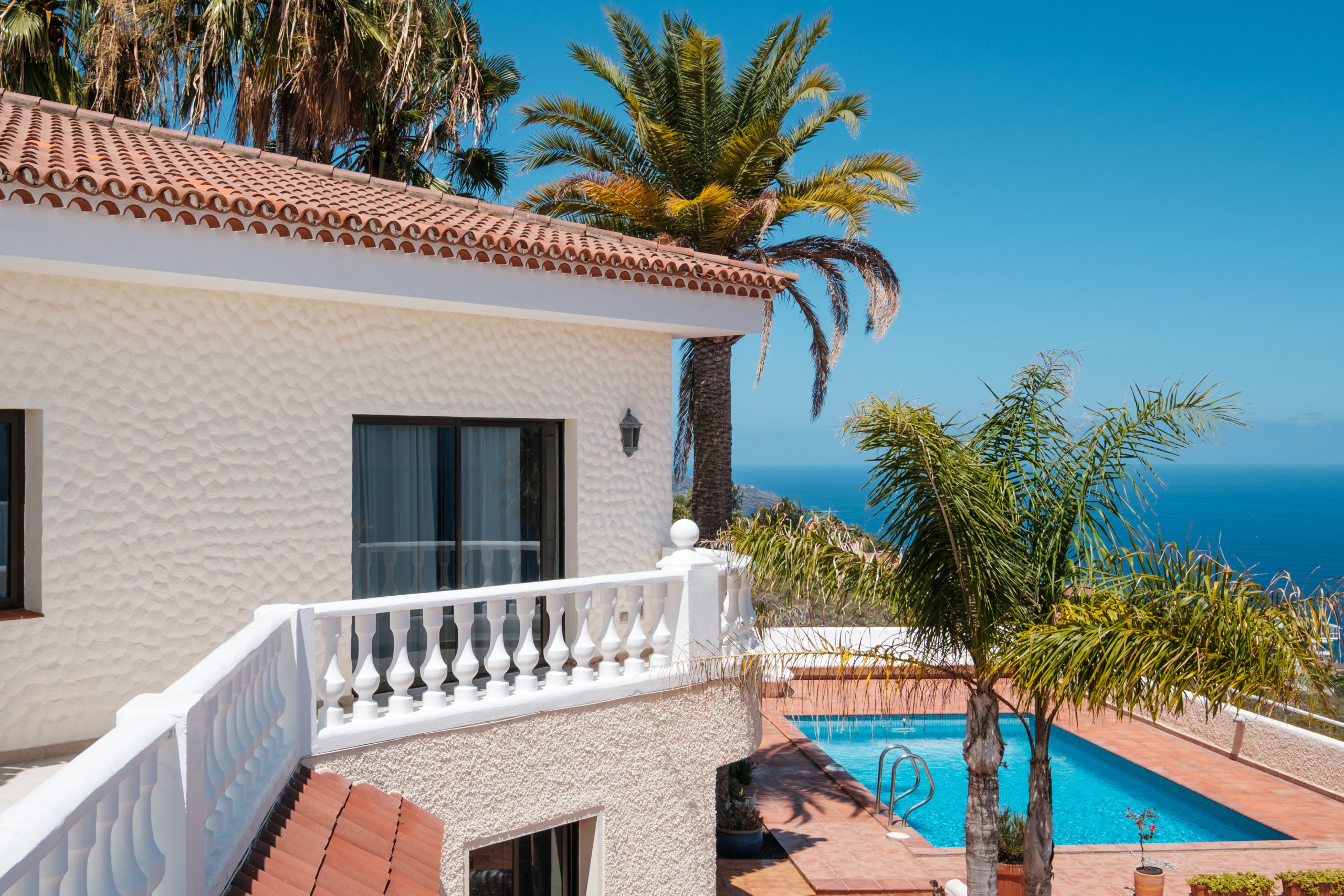 house with swimming pool, palm trees and ocean sea view